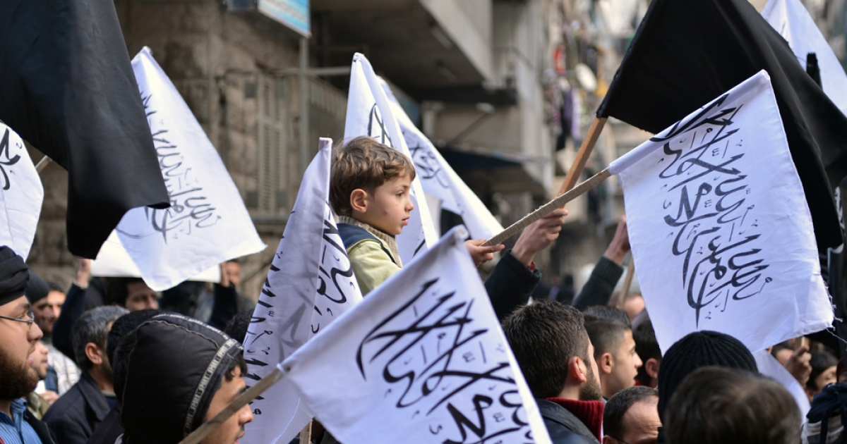 Syrian supporters of the Al-Nusra group wave flags as they march during an anti-regime demonstration in Aleppo on Feb. 8, 2013.</p>