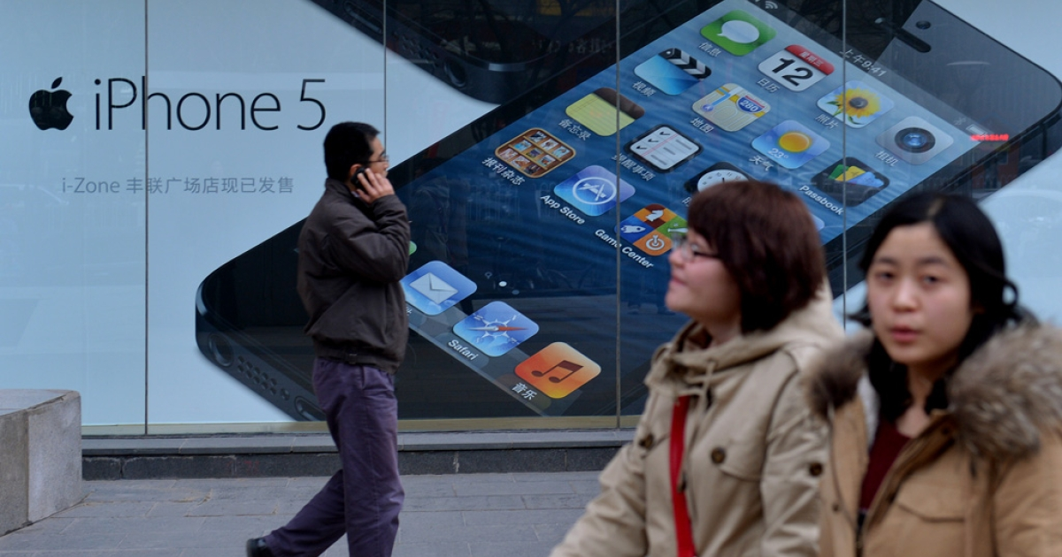 Shoppers walk past an Apple reseller in Beijing on March 18, 2013. Apple was recently targeted over its consumer-service practices in China during a state television broadcast focusing on consumer rights, allegedly claiming the US company treated its Chinese customers differently when it came to service and warranties.</p>