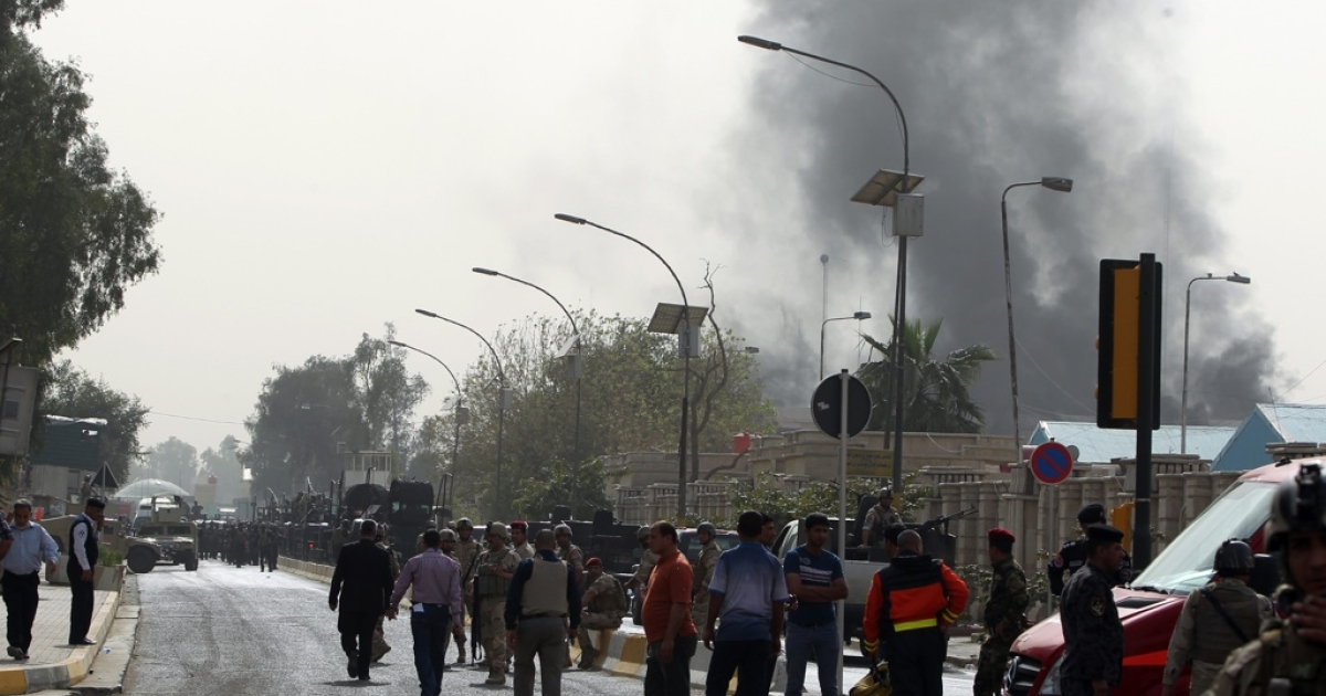 Smoke billows from the scene of a car bomb attack in Baghdad, on March 14, 2013. A coordinated string of bombings and brazen assault on a ministry near Baghdad's heavily fortified Green Zone killed 18 people, in the Iraqi capital's deadliest violence this month.</p>