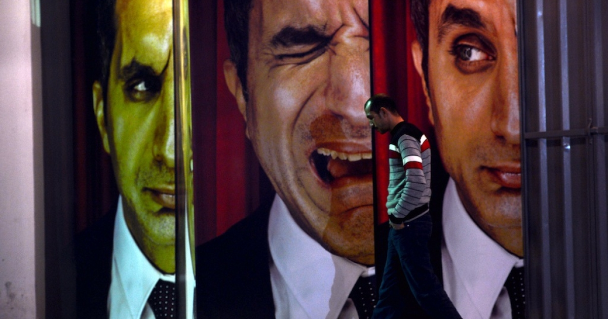 An Egyptian walks past posters of Egyptian satirist Bassem Youssef outside a theater in Cairo on January 22, 2013.</p>