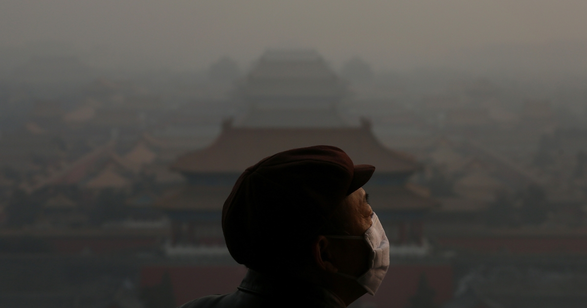 A tourist wearing the mask looks at the Forbidden City as pollution covers the city on Jan. 16, 2013 in Beijing, China.</p>