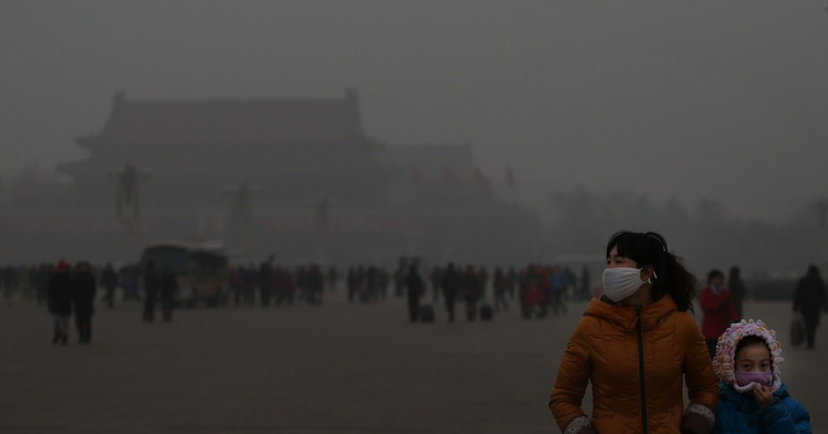 A tourist and her daughter wearing the masks visit the Tiananmen Square at dangerous levels of air pollution on Jan. 23, 2013 in Beijing, China.</p>