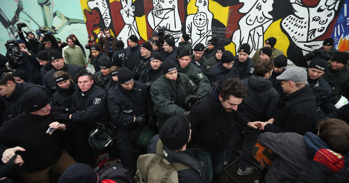 BERLIN, GERMANY - Protesters scuffle with police at the East Side Gallery, which is the longest still-standing portion of the former Berlin Wall, following efforts by a construction company to remove a 25-meter long section of the Wall on March 1, 2013 in Berlin, Germany. A real estate developer is planning to build a 14-storey apartment building between the East Side Gallery and the Spree River, and needs to remove the Wall section in order to allow access to the construction site.</p>
