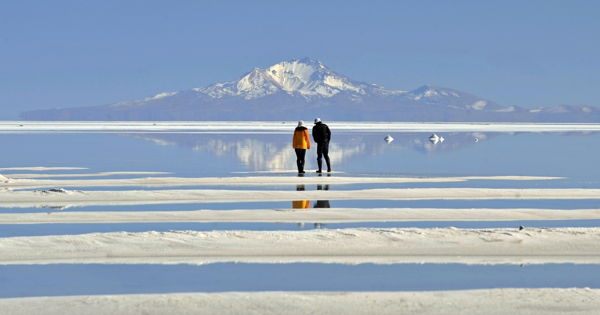 A Japanese tourist couple walks on Bolivia's Uyuni, the world's largest salt flat said to also have one of the richest deposits of lithium.</p>
