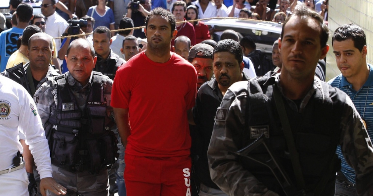 Brazilian footballer Bruno Fernandes de Souza (in red) is taken into custody to the presidium of Belo Horizonte, Brazil, on July 9, 2010. De Sousa, a star goalkeeper for the popular Brazilian club Flamengo, surrendered to police Wednesday to face questioning in connection with the disappearance of his ex-girlfriend.</p>