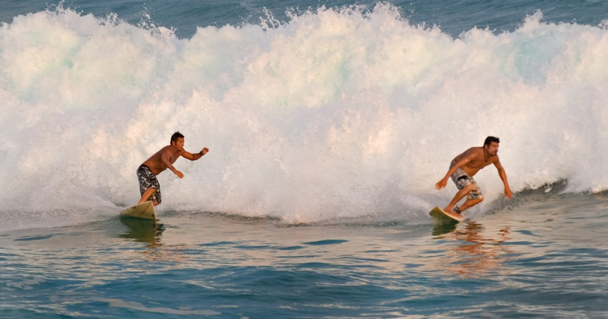 Two surfers ride waves at Cabo San Lucas in Mexico on October 18, 2009. The tourist city is a popular destination for US spring breakers.</p>