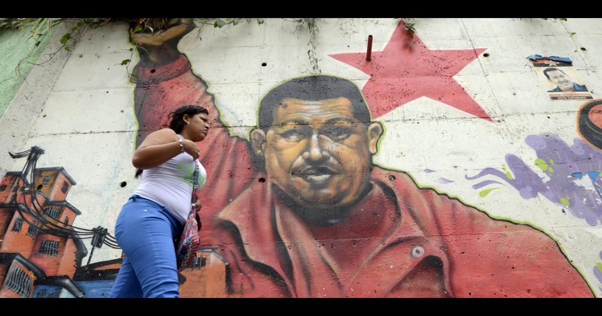 A woman walks past a mural of Venezuelan President Hugo Chavez in Caracas on Jan. 1, 2013.</p>