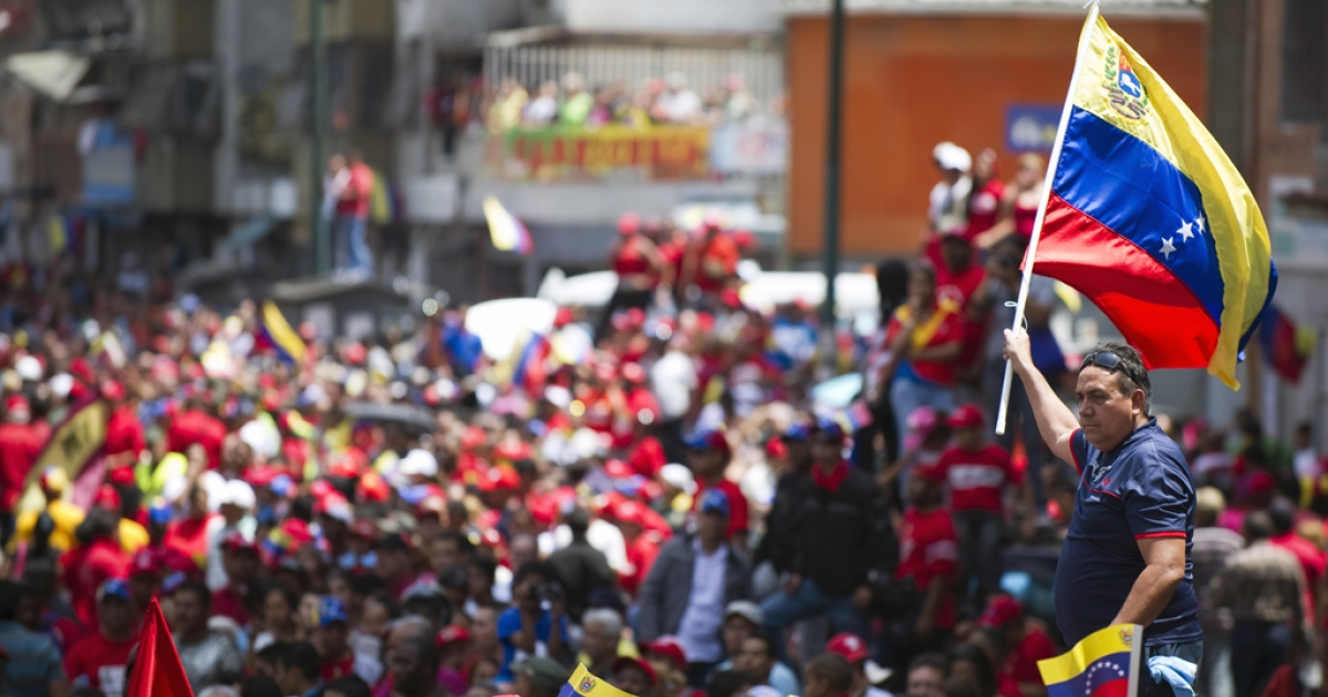 Thousands of supporters of the late Venezuelan President Hugo Chavez accompany the funeral cortege on its way to the Military Academy, on March 6, 2013, in Caracas. The flag-draped coffin of Venezuelan leader Hugo Chavez was borne through throngs of weeping supporters on Wednesday as a nation bade farewell to the firebrand leftist who led them for 14 years.</p>