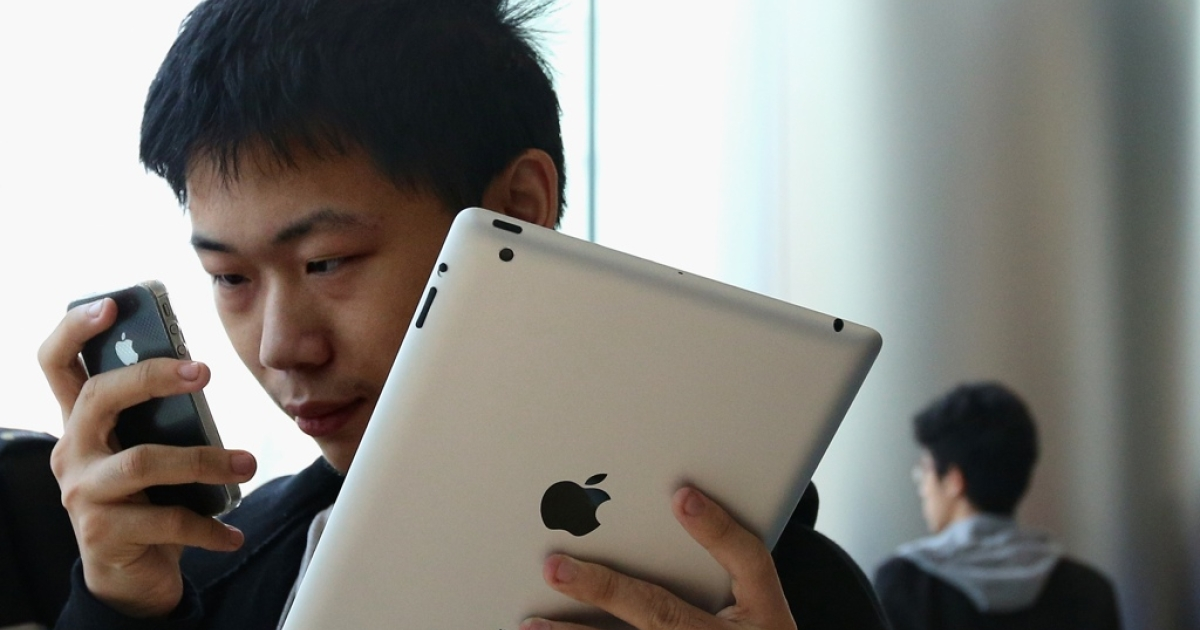 In Beijing's Wangfujing Apple Store, a Chinese customer looks at an iPhone 4S in one hand, with an iPad in other.</p>