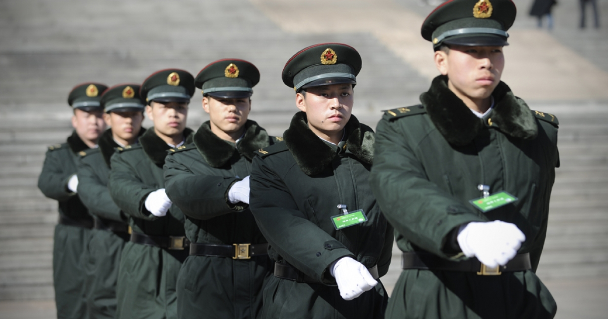 A group of soldiers make their way in front of the Great Hall of the People in Beijing on March 4, 2013.</p>