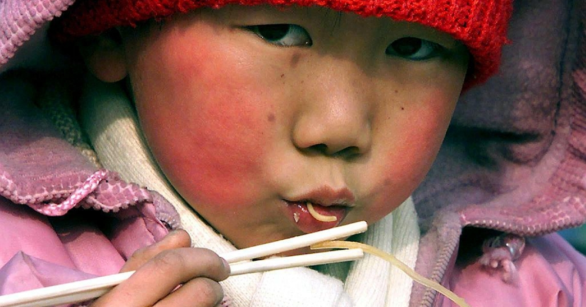 A young Chinese boy sucks up a bowl of noodles (Stephen SHAVER/AFP/Getty Images)</p>