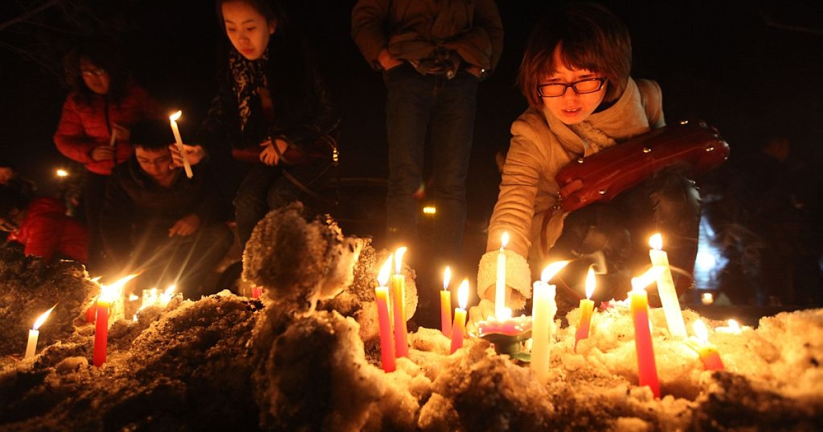 This picture taken on March 5, 2013 shows Changchun citizens gathered together to mourn the death of a two-month-old baby killed by a car thief in Changchun, northeast China's Jilin province. The thief strangled the baby to death after stealing a vehicle with the infant inside, police said, provoking outrage across the country on March 5, 2013. (STR/AFP/Getty Images)</p>