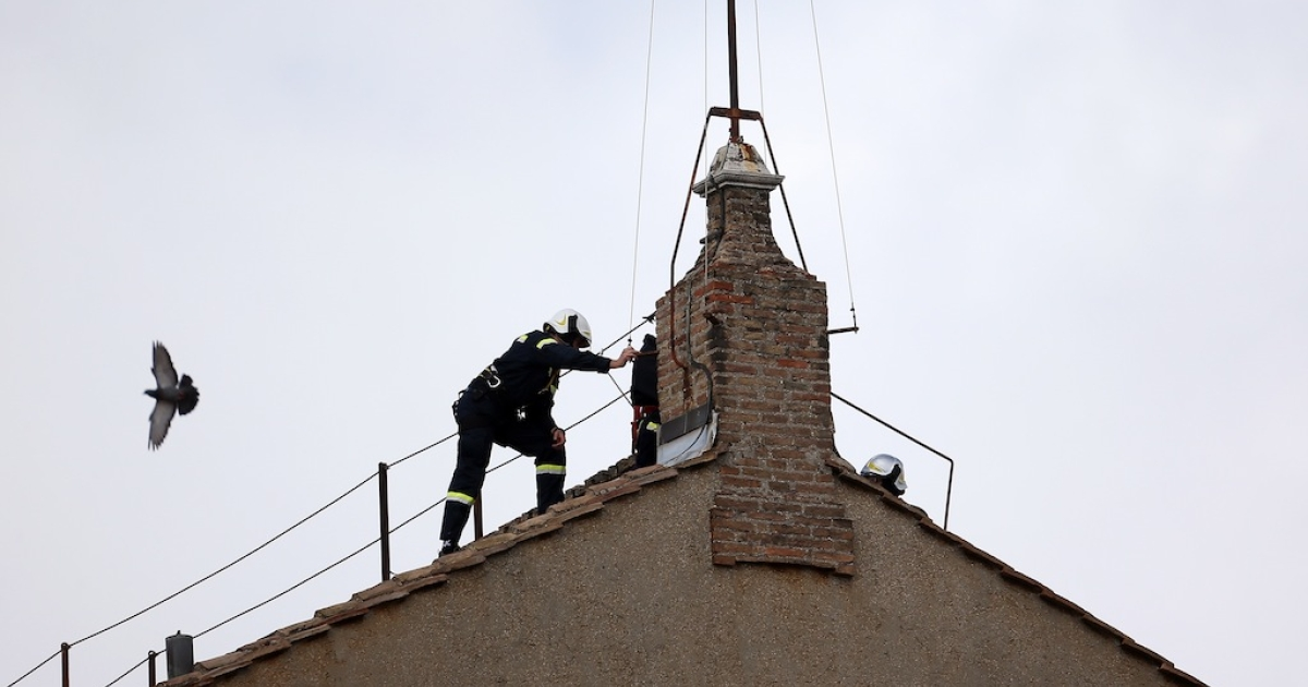 Members of the Vatican Fire Brigade install the chimney on the top of the Sistine chapel which will emit smoke as cardinals vote for a new pope on March 9, 2013 in Vatican City, Vatican.</p>