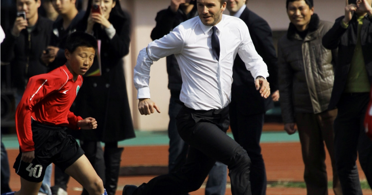 David Beckham plays with a group of Chinese youngsters during a promotional event in Tiantai Stadium in Qingdao, Shandong province, on March 22, 2013.</p>