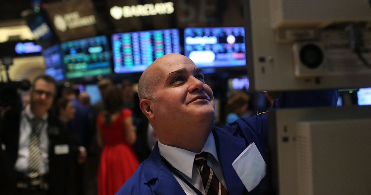 A trader smiles while working on the floor of the New York Stock Exchange. The Dow Jones industrial hit an all-time high on March 5, 2013, surpassing levels last seen in 2007.</p>