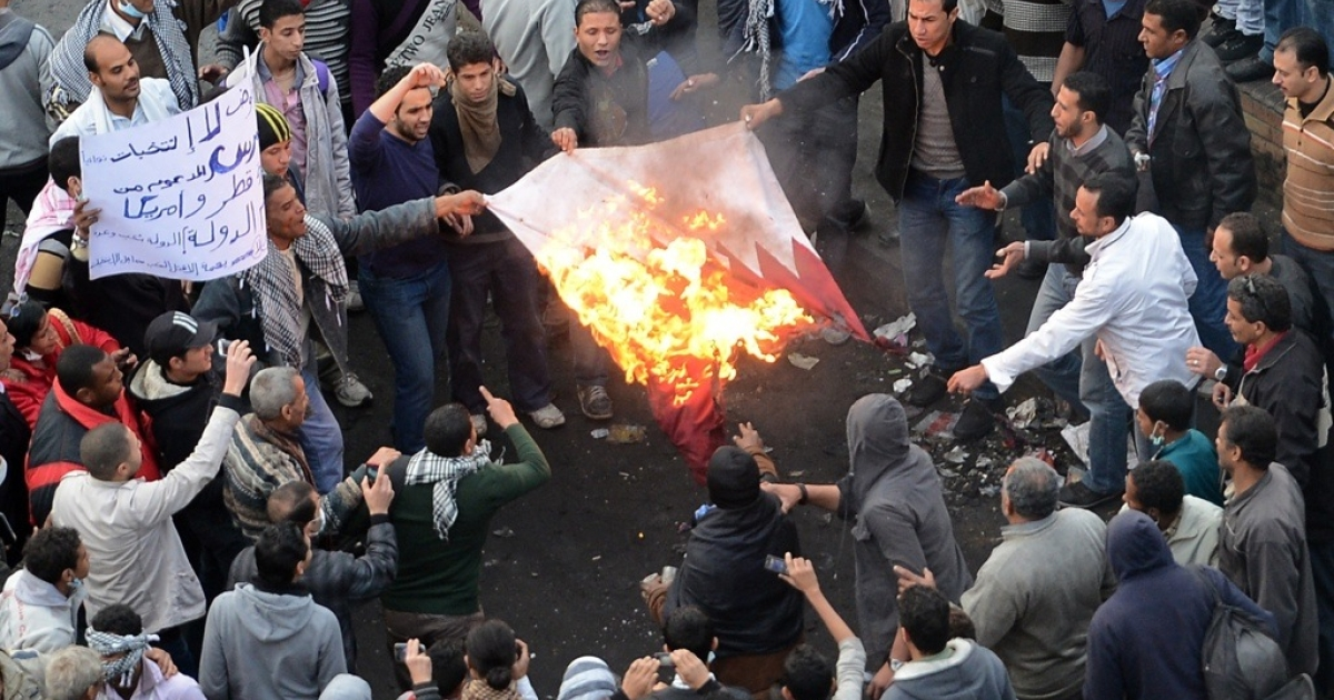 Egyptian protesters burn the Qatari flag in Cairo's Tahrir Square on Jan. 27, 2013.</p>
