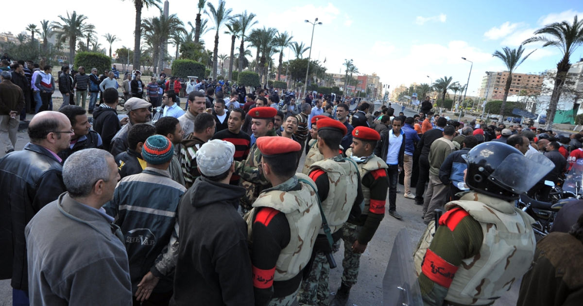 Egyptian military police men speak to protestors in the Egyptian city of Port Said on March 6, 2013 following clashes between police and protesters. Police and protesters lobbed rocks at each other under a volley of tear gas that caused several people to collapse.</p>