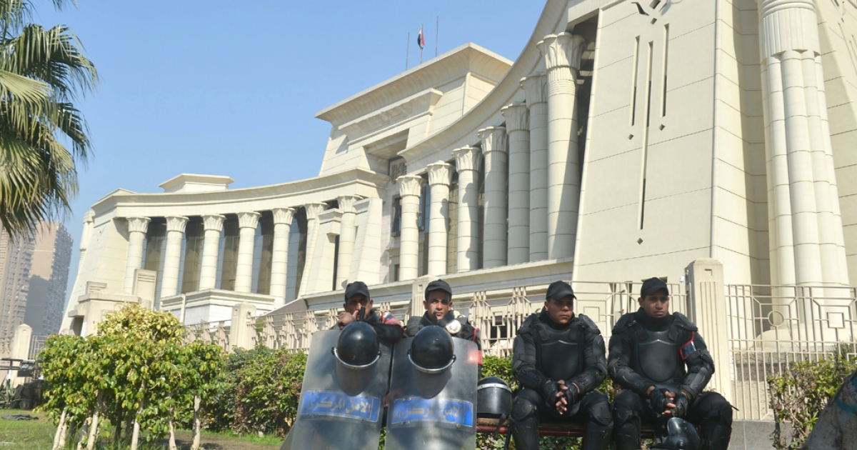 Egyptian riot police sit outside the high constitutional court in Cairo on February 3, 2013.</p>