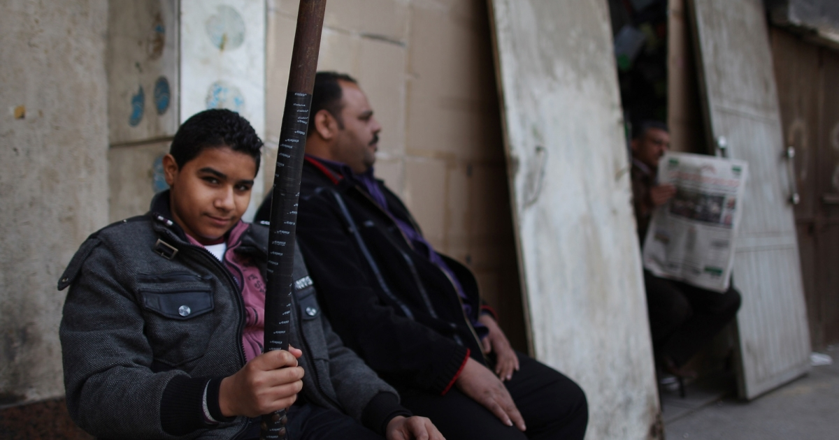 A boy holds a cudgel as he helps his father guard a property in Cairo, Egypt.</p>