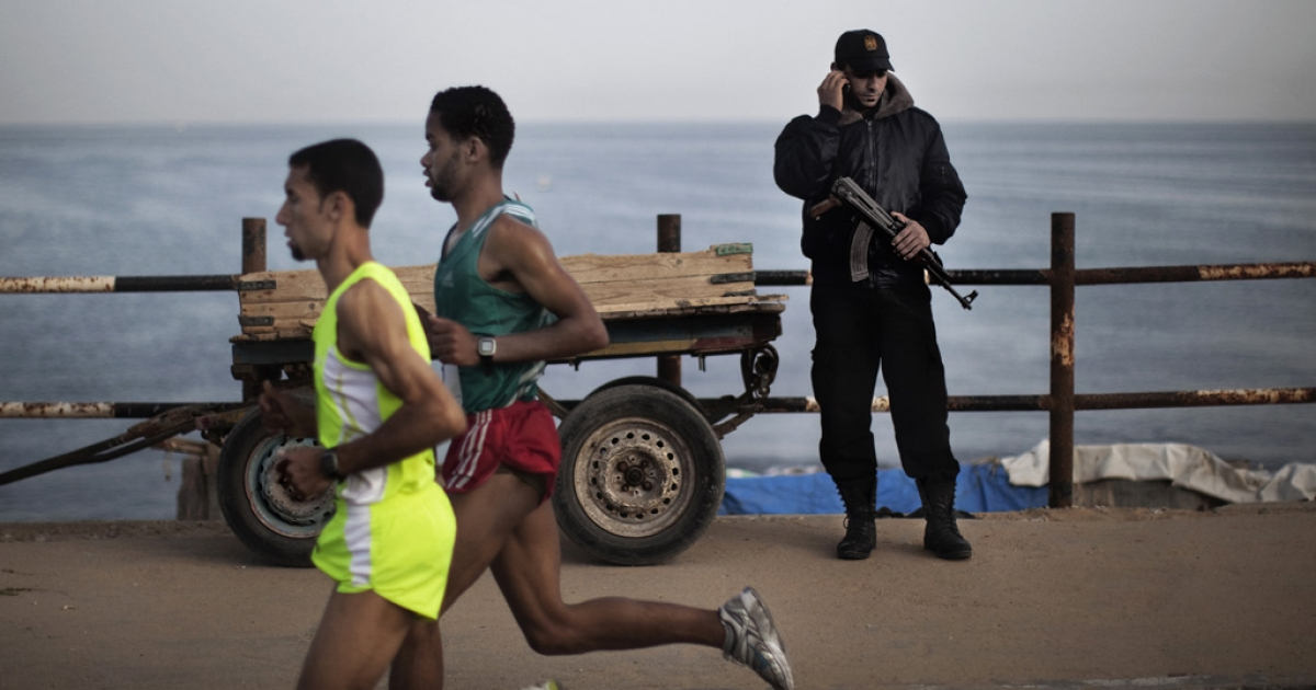 A Hamas policeman talks on the phone as Palestinian Olympic athlete Nader Masri, left, races along the waterfront in Gaza City on May 5, 2011 as they compete in the Gaza Strip's first-ever marathon which runs the entire length of the coastal enclave.</p>