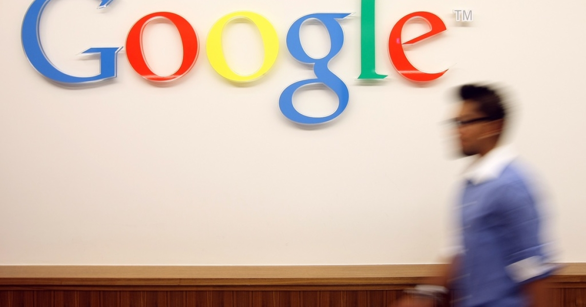 A visitor passes the Google logo on September 26, 2012 at the official opening party of the Google offices in Berlin, Germany.</p>