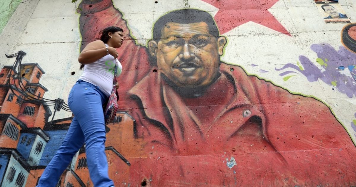 A woman walks past a mural of Venezuelan President Hugo Chavez in Caracas.</p>