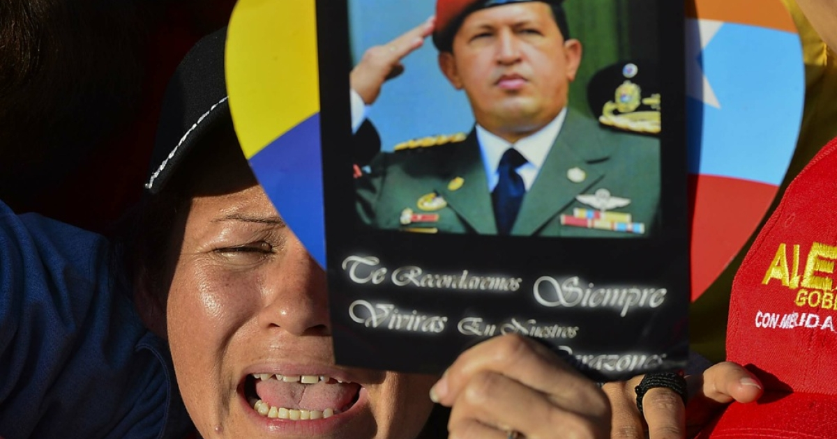 A supporter holds a picture of the late President Hugo Chavez, reading 'We shall always remember. You shall live in our hearts', outside of his funeral in Caracas, on March 8, 2013.</p>