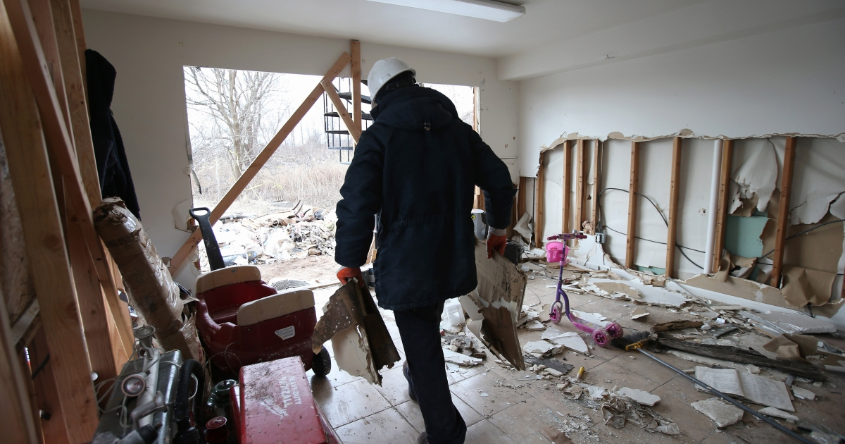 A laborer removes debris from a home damaged by Superstorm Sandy on January 4, 2013 in the Midland Beach area of the Staten Island borough of New York City. More than two months after the storm, Congress passed legislation today that will provide $9.7 billion to cover insurance claims filed by people whose homes were damaged or destroyed by Sandy.  (Photo by John Moore/Getty Images)</p>