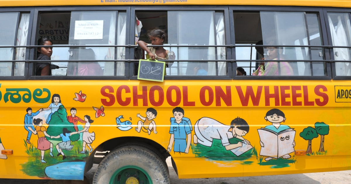Indian children study inside a bus converted to a school called the