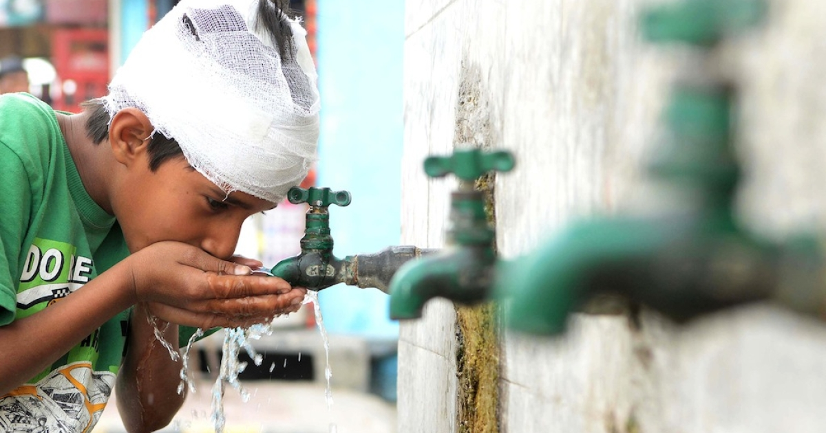 An Indian boy drinks water from a tap on the roadside in Amritsar on March 22, 2013, World Water Day. Eighty percent of sewage in India is untreated and flows directly into the nation's rivers, polluting the main sources of drinking water.</p>
