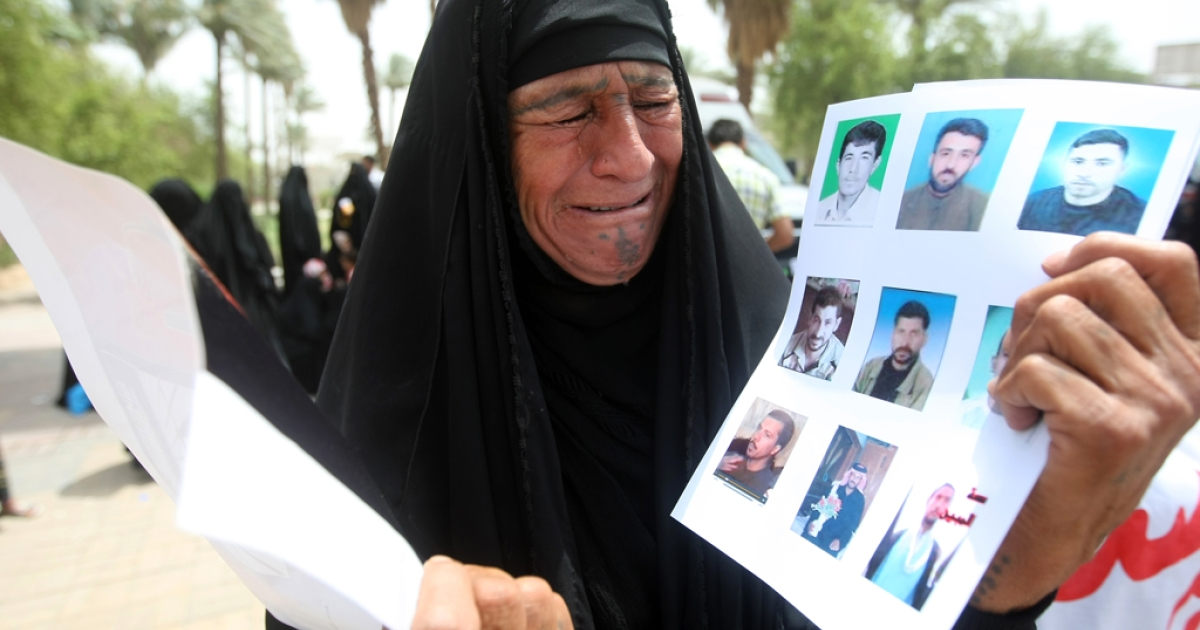 An Iraqi woman cries as she holds pictures of prisoners during a demonstration at Baghdad's Tahrir Square on July 1, 2011. Protesters called for the pardon or retrial of these prisoners, saying they were sentenced after confessing to their charges under torture.</p>