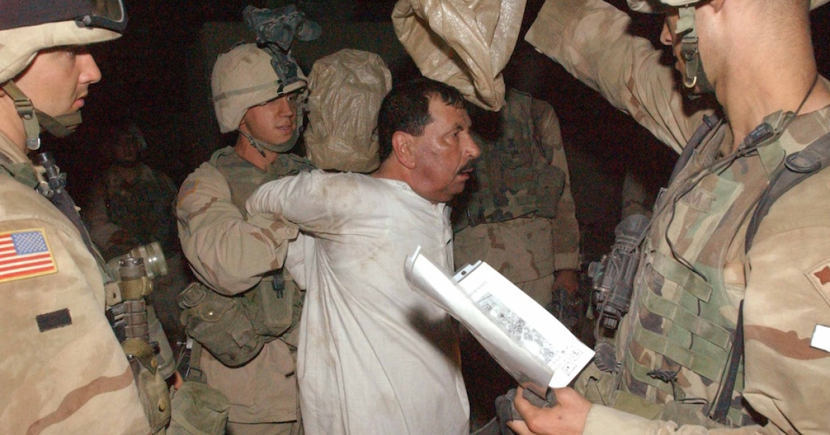 In this photo from July, 2003, American forces escort a detained Iraqi to a detention center at Forward Operation Base (FOB) in Balad, 76 km north of Baghdad, Iraq. Since the beginning of the war ten years ago, human rights abuses by US, coalition and Iraqi forces against the people have not stopped.</p>