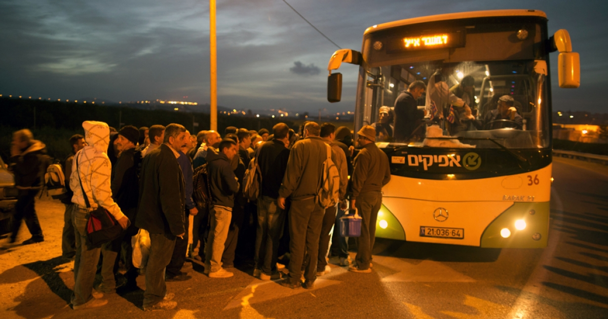 Palestinians queue to board a bus as a new line is made available by Israel to take Palestinian laborers from the Israeli army crossing Eyal, near the West Bank town of Qalqilya, into the Israeli city Tel Aviv, on March 4, 2013. Thousands of Palestinians enter Israel to work every day after receiving permits, many of them in private vans. The new line will not be available for Jewish settlers.</p>