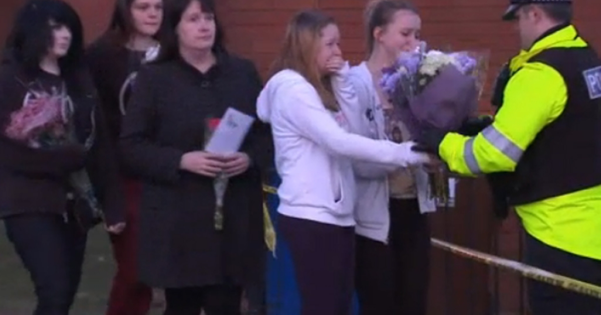 People give a policeman flowers at the home where 14-year-old Jade Anderson died on March 26, 2013, in Manchester, England. Police said they suspect a pack of five dogs killed Jade.</p>