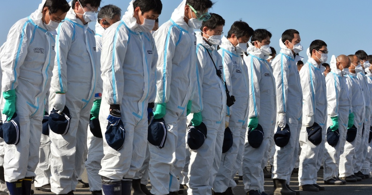 Police officers in radiation protection suits bow their heads to offer prayers in silence for tsunami victims in Fukushima on March 11, 2013.</p>