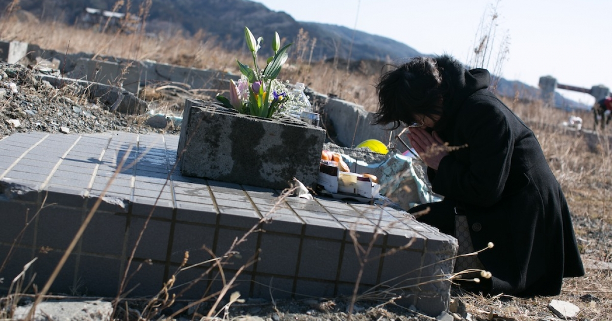 A woman prays for her family where her house used to stand on March 11, 2013 in Ootsuti, Iwate prefecture, Japan.</p>