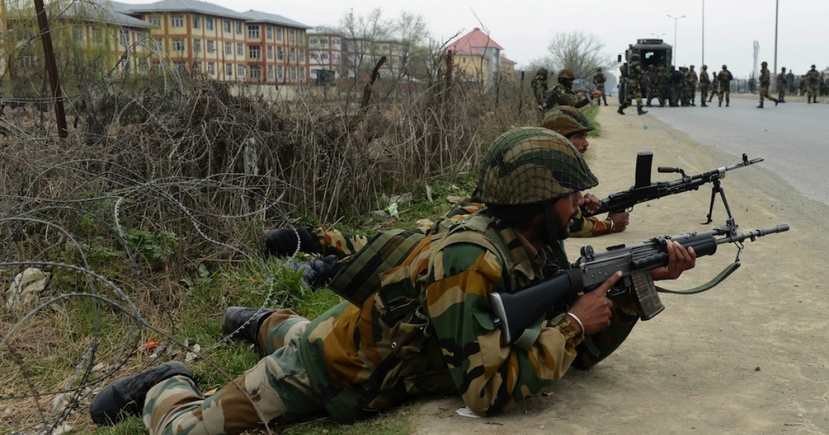 Soldiers take positions outside a school after an attack against Indian paramilitary personnel in Srinagar on March 13, 2013.</p>