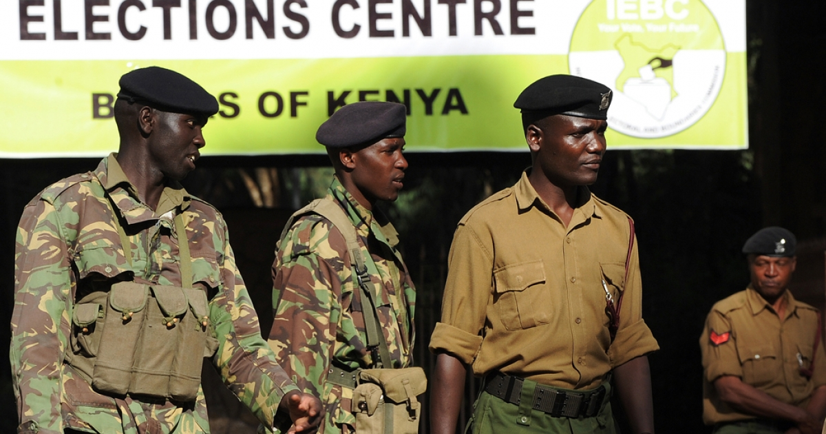 Kenyan Police officers stand guard at the entrance of a polling station where Independent Electoral and Boundaries Commission (IEBC) officers work on March 7, 2013 in Nairobi. Kenya's presidential election was plunged into further disarray today after the party of one of the leading candidates alleged vote-rigging and demanded that the count be halted.</p>