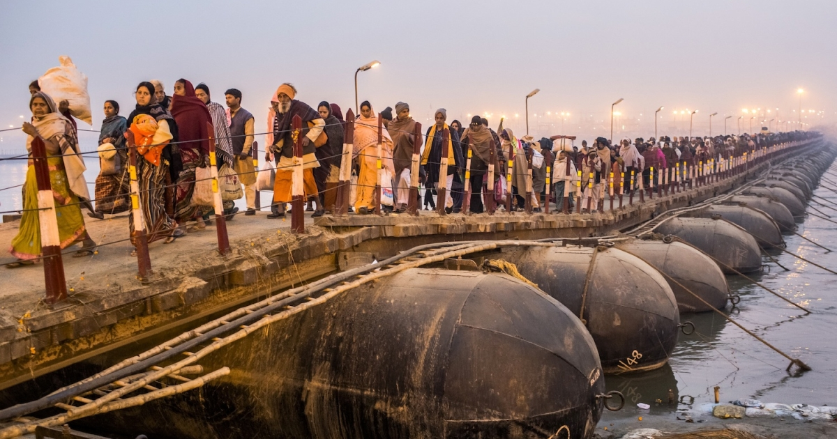 ALLAHABAD, INDIA - FEBRUARY 12: Hindu pilgrims walk across a pontoon bridge as others bathe on the banks of Sangam, the confluence of the holy rivers Ganges, Yamuna and the mythical Saraswati, during the Maha Kumbh Mela on February 12, 2013 in Allahabad, India. The Maha Kumbh Mela, believed to be the largest religious gathering on earth is held every 12 years on the banks of Sangam, the confluence of the holy rivers Ganga, Yamuna and the mythical Saraswati. The Kumbh Mela alternates between the cities of Nasik, Allahabad, Ujjain and Haridwar every three years. The Maha Kumbh Mela celebrated at the holy site of Sangam in Allahabad, is the largest and holiest, celebrated over 55 days, it is expected to attract over 100 million people. (Photo by Daniel Berehulak/Getty Images)</p>