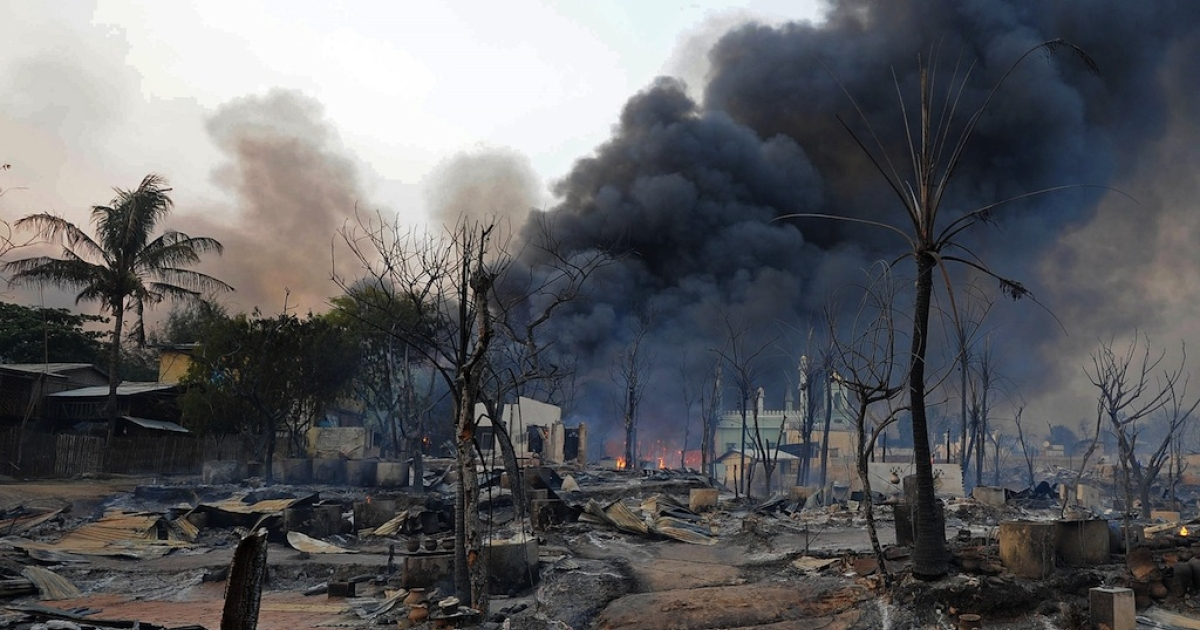 Black smoke rises from burning houses around a mosque in riot-hit Meiktila, central Myanmar on March 21, 2013.</p>