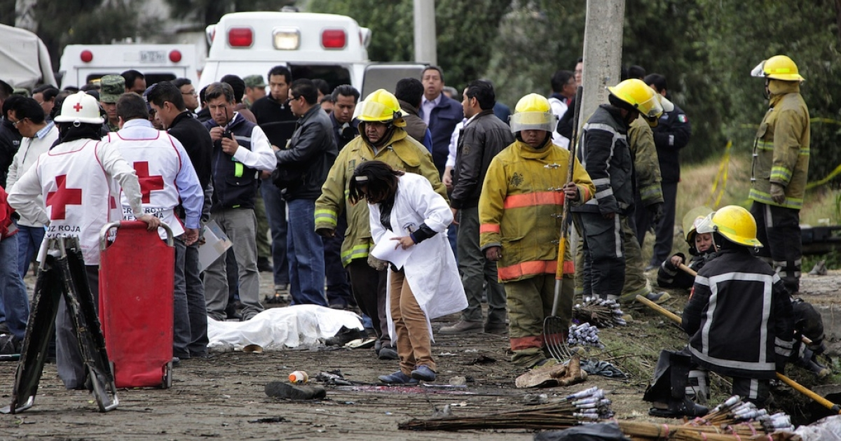 Emergency rescue workers stand near one of the victims of Friday's deadly fireworks explosion in central Mexico.</p>