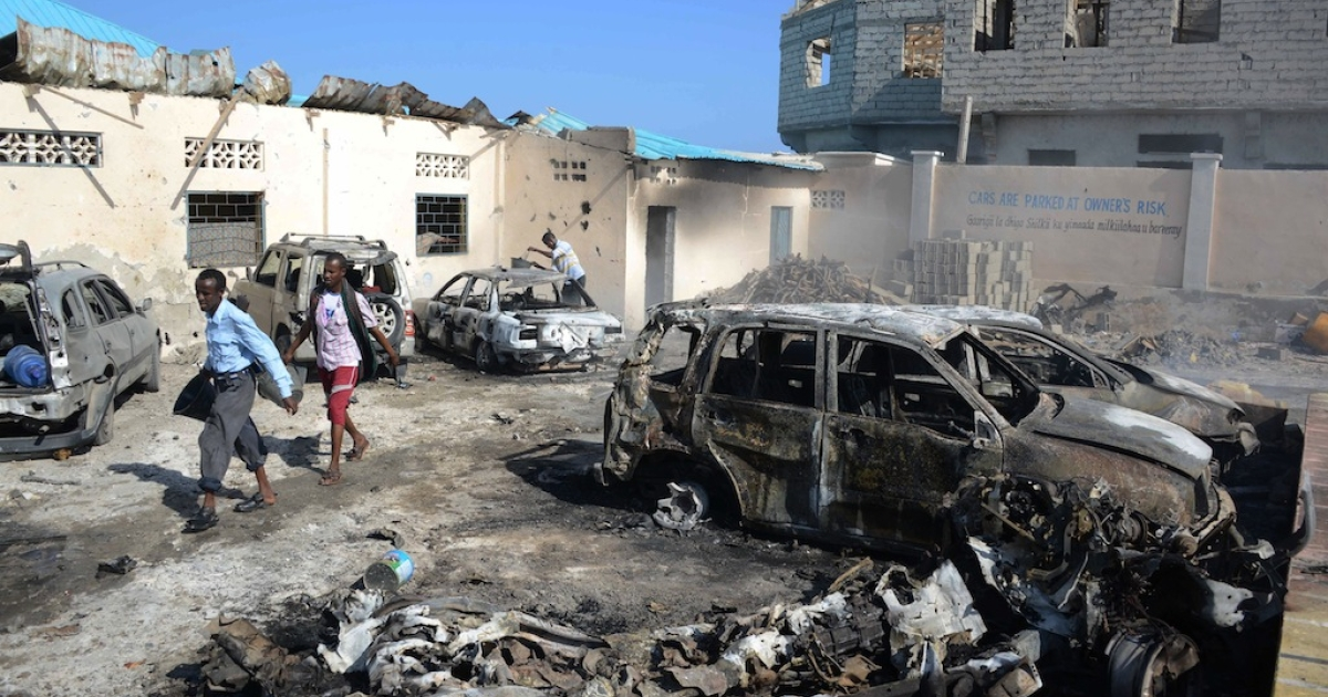 People walk past the scene of a car bomb explosion close to Mogadishu's famous Lido beach on Feb. 16, 2013.</p>