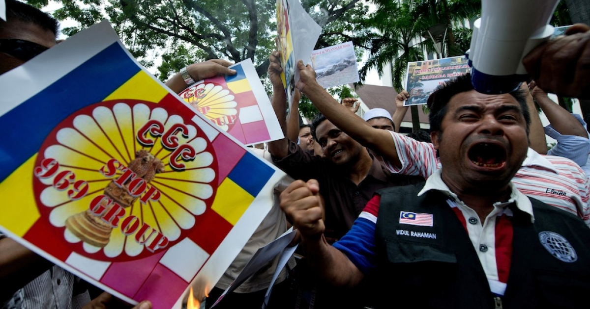 Myanmar ethnic Rohingya shout slogans and burn placards reading 'Stop 969 Group' during a protest in Kuala Lumpur on March 25, 2013.</p>