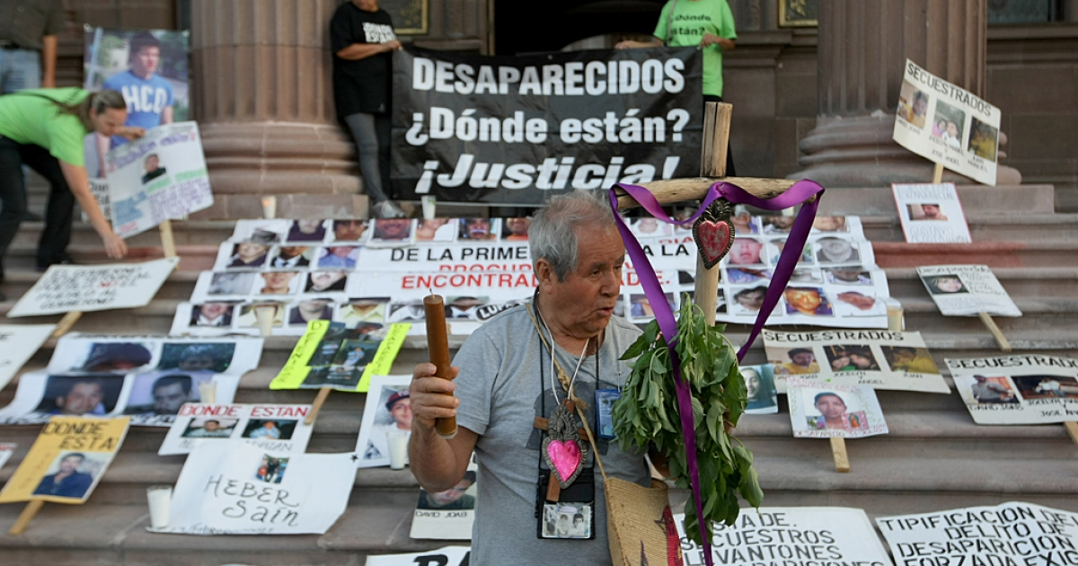 A man who has a missing relative holds a cross and a sign during a protest demanding information on the whereabouts of missing relatives, during the commemoration of the International Day of the Disappeared in Monterrey, Mexico, on Aug. 30, 2012.</p>