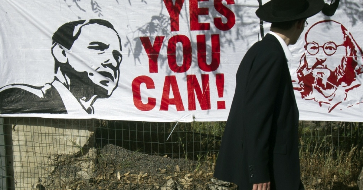 An Orthodox Jewish man walks past a banner on March 13, 2013 in Jerusalem.</p>