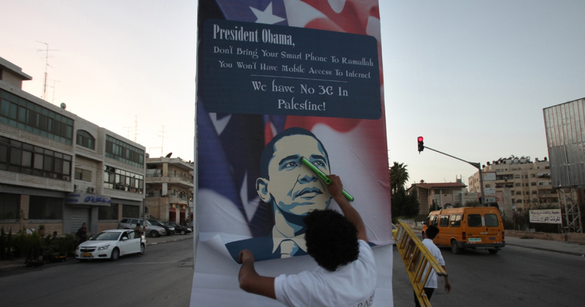 A Palestinian activist hangs up an anti-Obama poster in the West Bank city of Ramallah on March 11, 2013. Many Palestinians have middling expectations for US President Barack Obama's three-day visit to Israel and the Palestinian territories, a trip that will begin on March 20.</p>