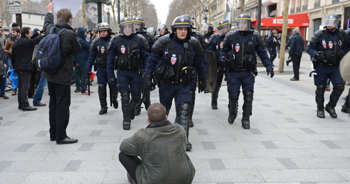 A man lays on the ground as riot police walk along the Champs-Elysees avenue during a demonstration against France's gay marriage law.</p>