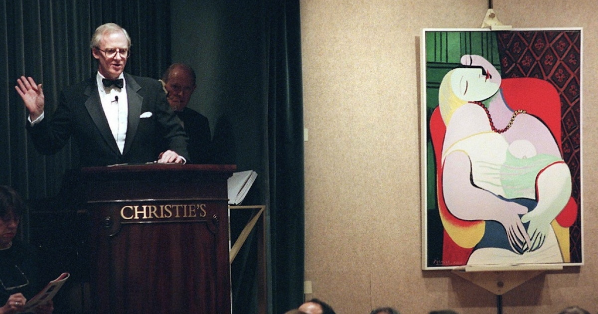 New York, UNITED STATES: File picture taken November 10, 1997 shows Christopher Burge, chairman of Christie's (L), starting the bidding for Pablo Picasso's painting, 'Le Reve' in New York at an auction of the collection of Victor and Sally Ganz.</p>