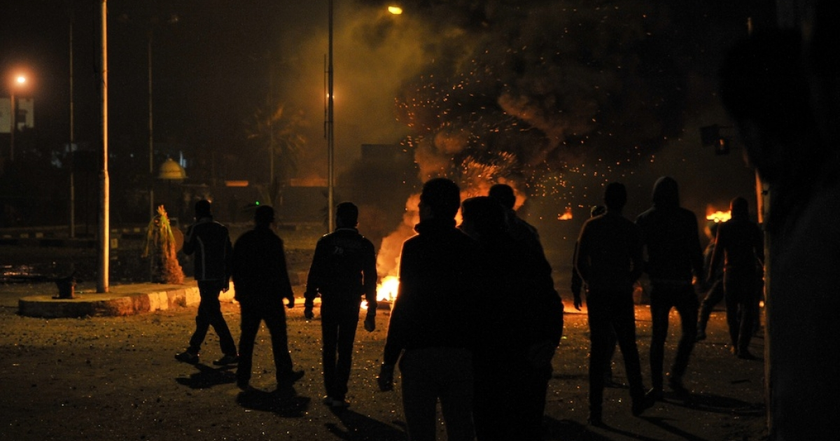 Egyptian protesters stand near burning tyres outside the main security headquarters in the canal city of Port Said on March 5, 2013.</p>