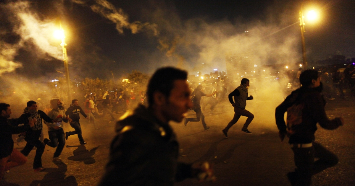 Egyptian protesters run for cover from tear gas fired by riot police during clashes in Cairo, on March 8, 2013. Egyptian Interior Minister Mohamed Ibrahim sacked the riot police chief amid strikes by policemen who complained they are ill-equipped to confront protesters, state media reported.</p>